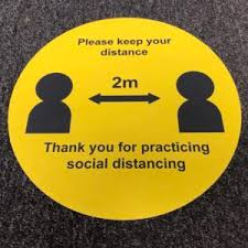 A yellow social distance floor marker circle with the words ' please keep your distance, thank you for practicing social distancing' and a black and white outline of two stylized people and a double headed arrow between them which has 2m above it.